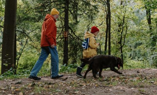 Grandparent and child hiking with dog