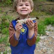 young boy holding up a rock with fossils