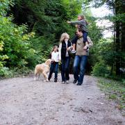 family with dog taking a walk on gravel path